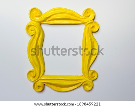 Yellow photo frame or mirror frame with a white background, to frame texts or images.