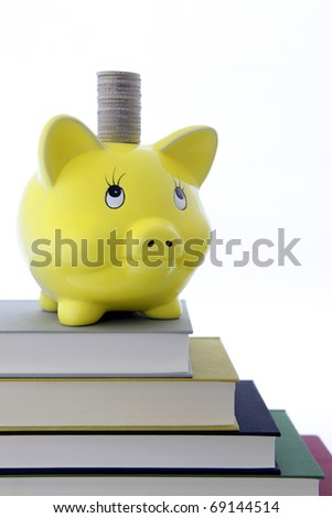 Yellow Piggy bank on a pile of books