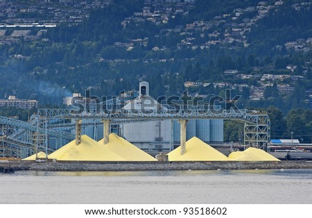 Yellow piles against blue silos in front of the mountains.