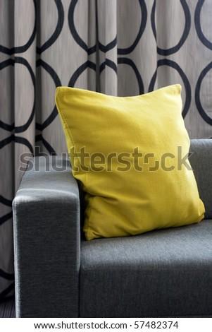 Yellow pillow on gray sofa