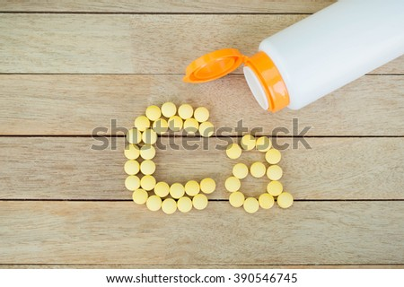 Yellow pills forming shape to Ca alphabet on wood background