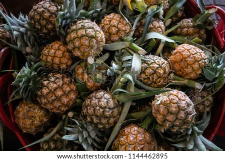 yellow pineapple type of tropical fresh fruits , heap of organic nutrition diet fruit at asian market in Thailand . common useful vitamin for good foods .