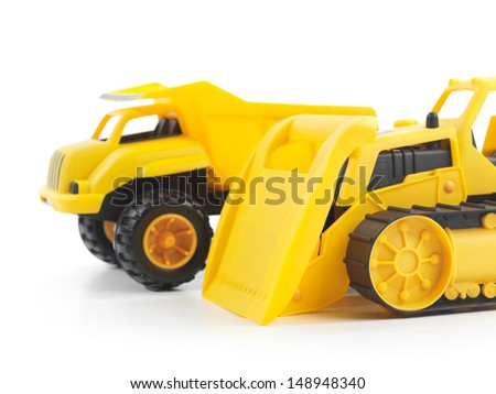 Yellow plastic children toys a bulldozer and a dump truck isolated on white background