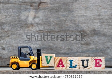 Yellow plastic forklift hold letter V to complete word value on wood background
