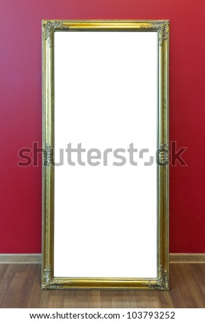 Yellow plastic mass production frame from  large mirror stand  against a red office wall. With patch