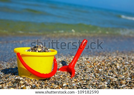 Yellow plastic spade and green bucket in sand