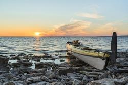 Yellow plastic tandem sea kayak parked on rocky shore. Sunset glow on the Baltic Sea water. North coast of tiny Kesselaid (Kessulaid) islet in Suur Strait. Typical Estonian coastline. Dawning sky.