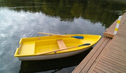 Yellow pleasure boat in the pond. Rowing boat. Recreation park. Summer day. Water recreation. Rowing.