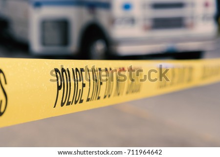 Yellow police line do not cross crime scene tape with emergency vehicle in background, wet with rain drops. - Shutterstock ID 711964642