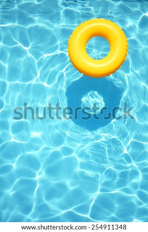 Yellow pool float, ring floating in a refreshing blue swimming pool #254911348