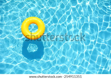 Yellow pool float, ring floating in a refreshing blue swimming pool #254911351