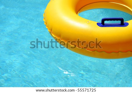 Yellow pool float/ring in pretty blue swimming pool - stock photo