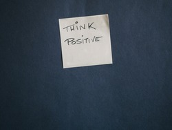 Yellow post it with positivism message on black background