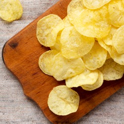 Yellow potato chips with salt on a rustic wooden board, overhead view. Flat lay, top view, from above. Close-up.