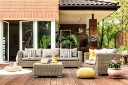 Yellow pouf next to a rattan armchair and flowers on wooden patio with striped pillows on sofa