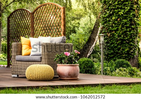 Yellow pouf next to a rattan armchair with grey and gold pillows and pink flowers on wooden veranda