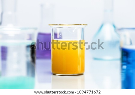 Yellow precipitate in a beaker, surrounded by various chemical lab glassware. #1094771672