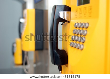 yellow public telephones with emergency icons