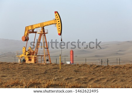 Yellow pumpjack -overground drive of a piston pump- lifting oil from a well in the Tazhong Oil Field of the Taklamakan Desert near the Taqie Hiighway-branch of the Tarim Desert Highway. Xinjiang-China