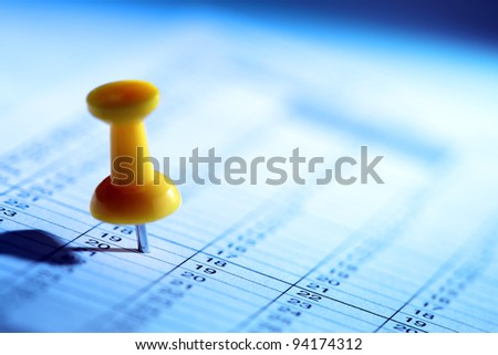 Yellow push pin in a date on calendar or planner