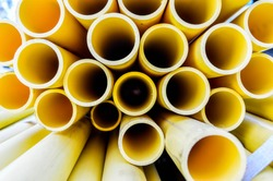 Yellow PVC tubes in storage, Plastic tubes, Background of PVC