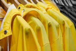 Yellow rain jackets hang on wooden hangers, closeup. Yellow and gray fashion background. Trendy Colors of the year 2021 Yellow Illuminating and Ultimate gray