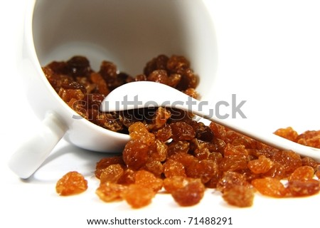 Yellow raisins with cup and spoon
