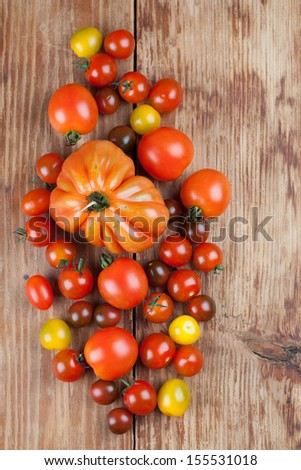 Yellow, red and black tomatoes on wooden background