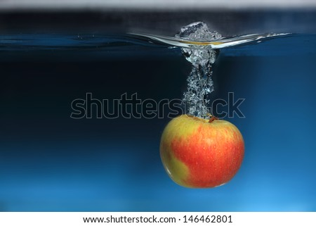 Yellow red apple in the water splash over blue background. Healthy food and active life.