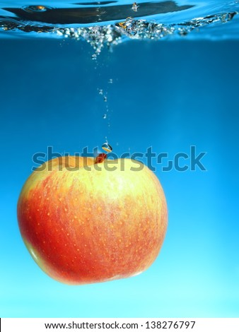 Yellow red apple in the water splash over blue background. Healthy food and active life. Square format