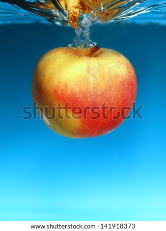 Yellow red apple in the water splash over blue background. Healthy food and active life. Square format.