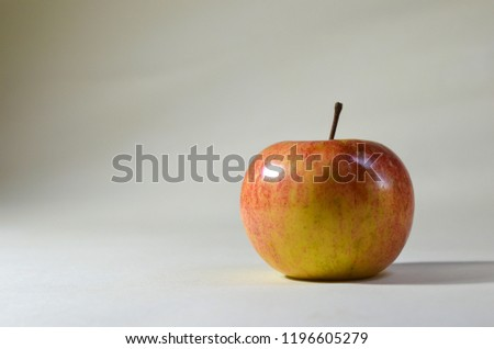 Yellow-red apple with glitter on a white background, located on a large burning object to the right of the object #1196605279