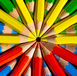 Yellow,red,blue and green colored pencils in the round formation on the black background close up .Macro photography.