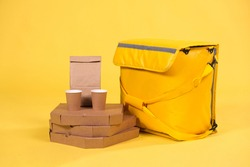 Yellow refrigerator bag for food delivery or for trip to nature and tourism on yellow background with food pizza and drinks in an eco-friendly paper packaging. Thermos bag protects food from spoilage