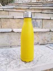 Yellow reusable steel bottle on stairs outdoor  close up