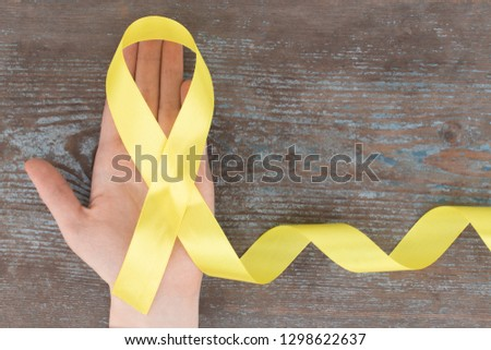yellow ribbon-childhood cancer awareness symbol on the wooden background with copy space.  #1298622637