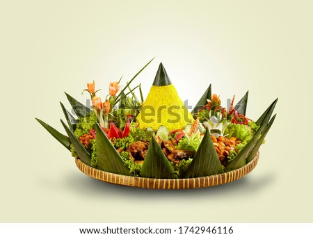 """Yellow rice in a cone shape. In Indonesia called """"Nasi Tumpeng"""" A festive Indonesian rice dish with side dishes. Tumpeng rice in a bamboo woven tray."""