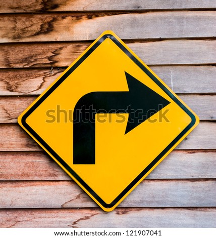 Yellow right turning traffic road sign on a wooden plank