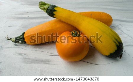 Yellow ripe zucchini and ripe tomato on a white acrylic background. Horizontal view