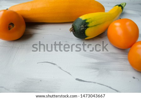 Yellow ripe zucchini and ripe tomatoes on a white acrylic background. Horizontal view