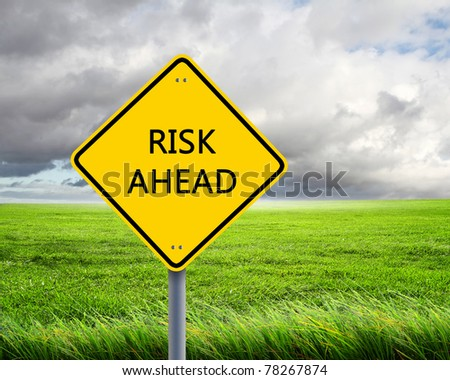 yellow road sign as a warning of risk ahead