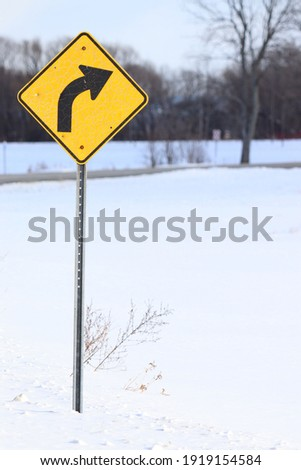 yellow road sign in Quebec showing the approach of a right turn during winter weather with snow on the ground Photo stock ©