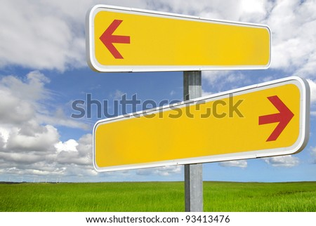 yellow roadsign with arrows on beautifull cloudy blue sky with green landscape