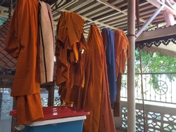 Yellow robes or clothes, dark yellow monks, sun-dried on the wire in front of the cloister in the temple at Thailand. Soft focus,Select focus