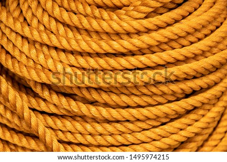 Yellow rope pile closeup photo. Ship or rock climbing tackle. Natural material woven cordage. Simple rope bulk concept. Alpine mountaineering equipment. Safety rope texture. Yacht tackle bundle card