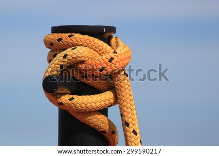 Yellow rope with black flecks tied around a large black post symbolizing boating, yachting and security