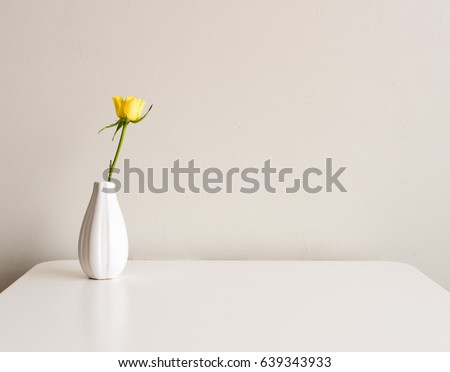 Yellow rose in small white vase on white table against neutral background