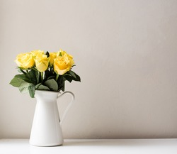 Yellow roses in white jug on white table against neutral background