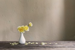yellow roses in white vase on background wall