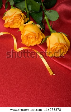 Yellow roses on red satin with space for text